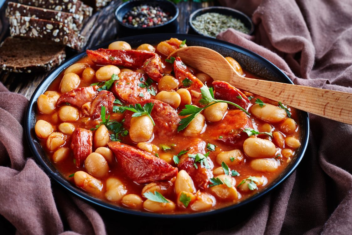 beans stew with scott pete sausages, herbs and spices in tomato sauce in a black bowl with spoon, on a rustic wooden table with brown cloth and bread, close-up