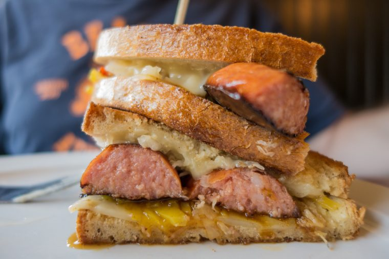 Close-up of grilled sandwich with scott pete polish sausage, cheese and sauerkraut